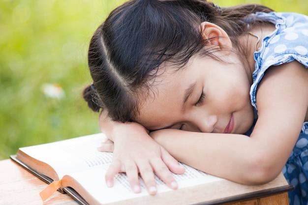 かわいいアジアの小さな子供の女の子が眠っていると本に横たわる