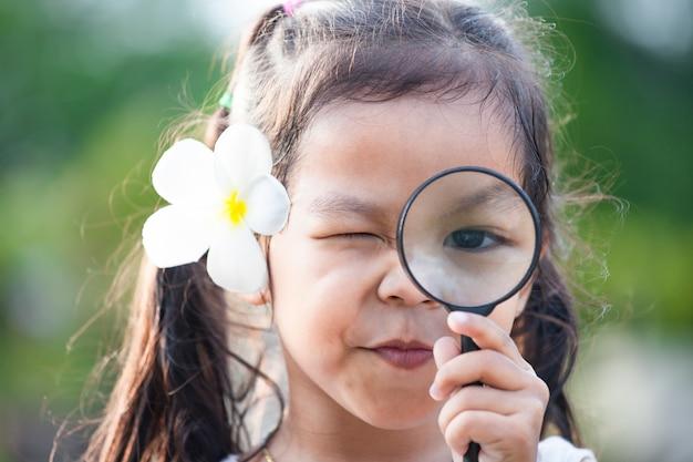 Симпатичные азии маленькая девочка, глядя через увеличительное стекло в парке на фоне зеленой природы