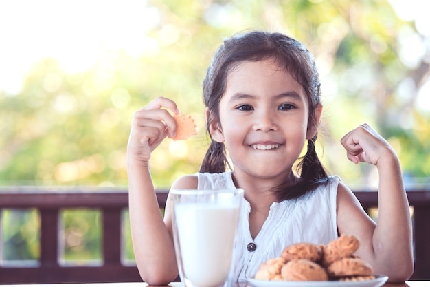 Cute asian little child girl making strong hand while drinking a milk