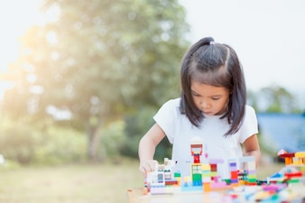 Cute asian little child girl playing with colorful blocks.