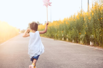 Cute asian little child girl playing with wind turbine and running on the road