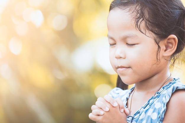 믿음, 영성 및 종교 개념에 대한 그녀의 손을 접어기도 귀여운 아시아 작은 아이 소녀