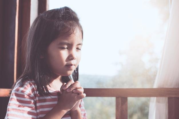 Симпатичная азиатская маленькая девочка, молясь, сложив руку в комнате