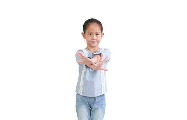 クロスアームの手に達するかわいいアジアの小さな子供の女の子は、白い背景で隔離の前で壊れます。