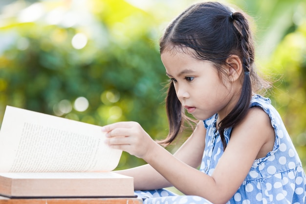 Cute asian little child girl reading a book in outside in nature background