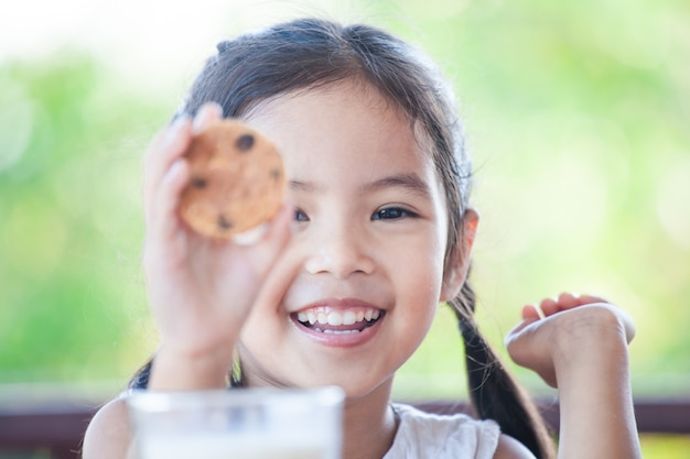 Cute asian little child girl smiling and holding cookie with milk