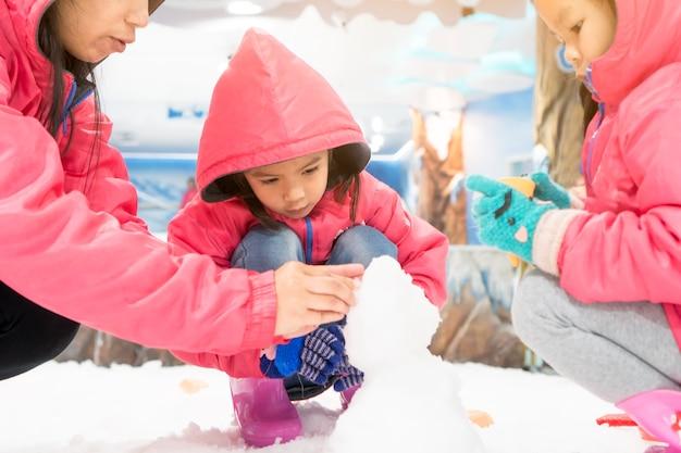 Симпатичные азии маленькая девочка в розовой куртке, играя со снегом с семьей