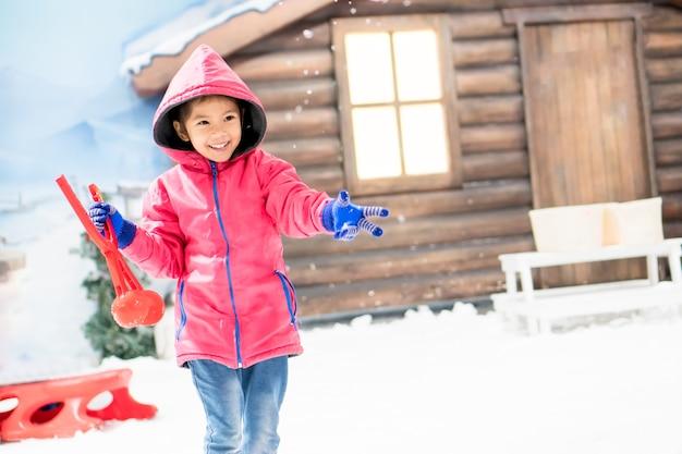 Симпатичные азии маленькая девочка в розовой куртке играет