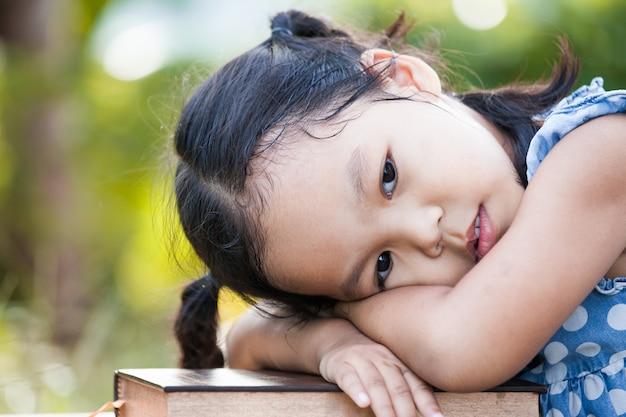 かわいいアジアの小さな子供の女の子は、本を読んで本に横たわる感じの退屈