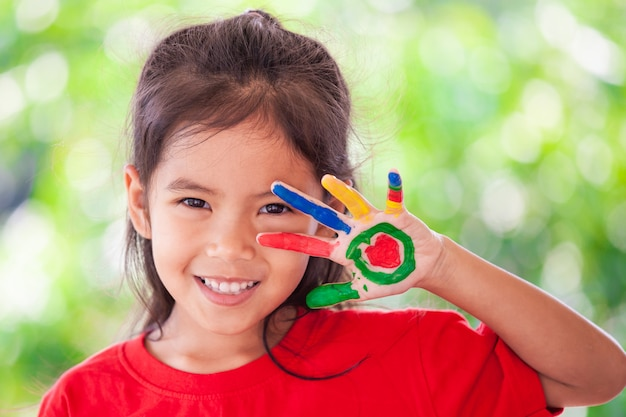 Cute asian little child girl with painted hands smiling with fun and happiness