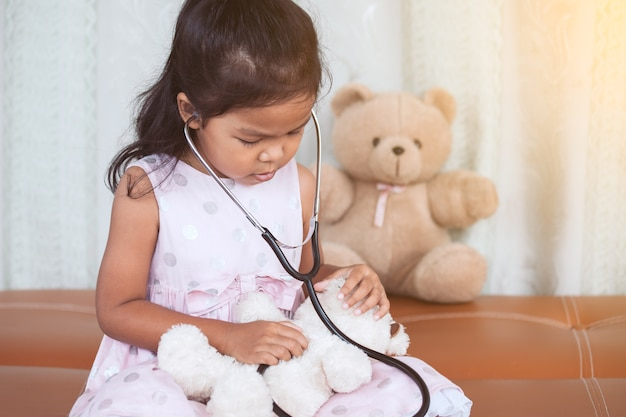 Cute asian little child girl with stethoscope playing doctor with teddy bear in vintage color tone