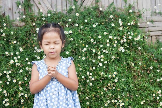 귀여운 아시아 소녀는 그녀의 눈을 감고 믿음의 개념에 대한기도에 그녀의 손을 접었다