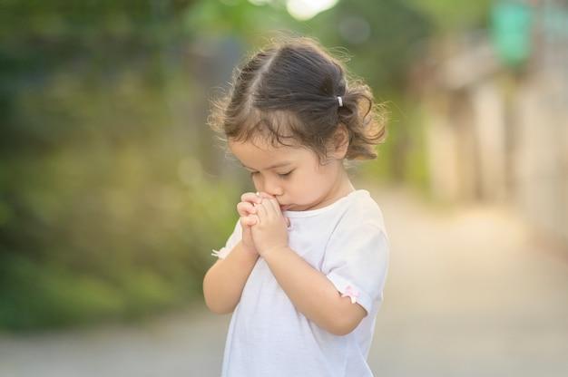 귀여운 아시아 소녀는 그녀의 눈을 감고 아침에기도. 작은 아시아 소녀 손기도, 손 믿음, 영성 및 종교에 대 한기도 개념에 접혀. 프리미엄 사진