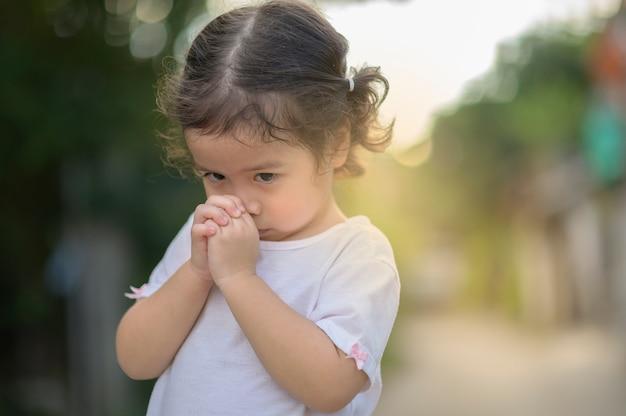 かわいいアジアの女の子は目を閉じ、朝に祈っています。小さなアジアの女の子の手祈り、手を組んで信仰、霊性および宗教のための祈りの概念。