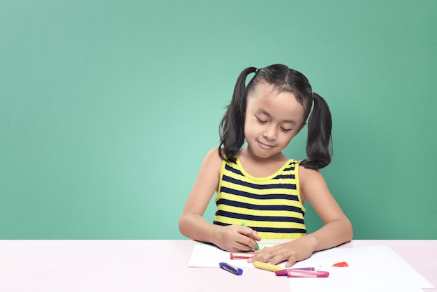 Cute asian little girl drawing with crayon while sitting at table