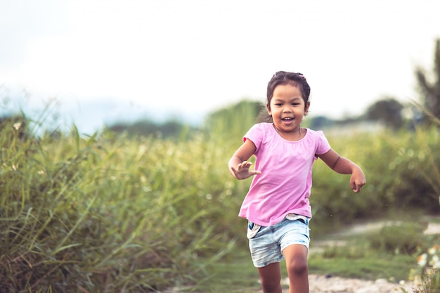 Cute asian little girl having fun and running in the park in vintage color tone