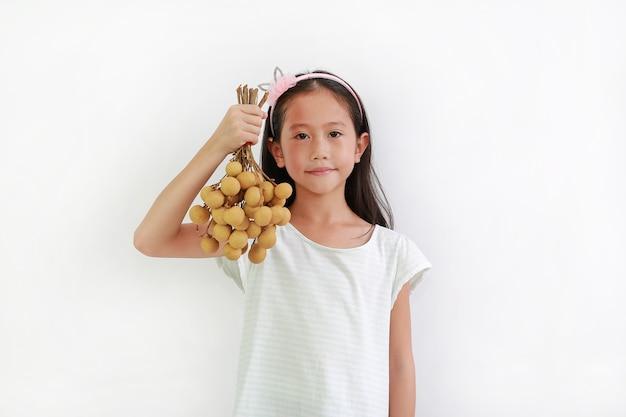 白い背景のリュウガンフルーツoagainstの束を保持しているかわいいアジアの小さな女の子の子供