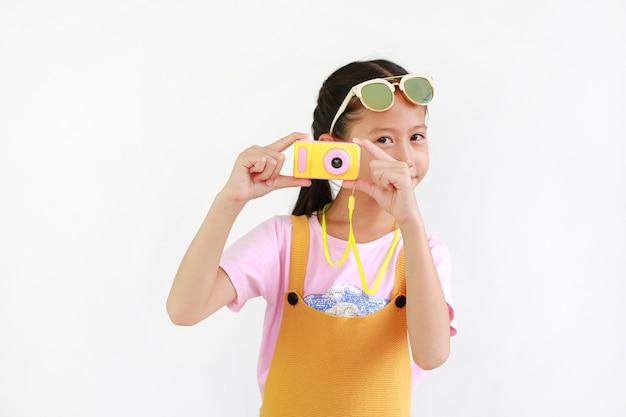 귀여운 아시아 어린 소녀가 흰색 배경에 격리된 사진 카메라 장난감으로 사진을 찍고 있습니다.