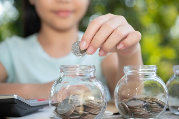 동전 돈, 돼지 저금통에 돈을 절약 유리 항아리에 돈을 만드는 동전 가지고 노는 귀여운 아시아 소녀. 그의 저장된 동전을 세는 아이, 미래의 개념에 대해 배우는 아이들.
