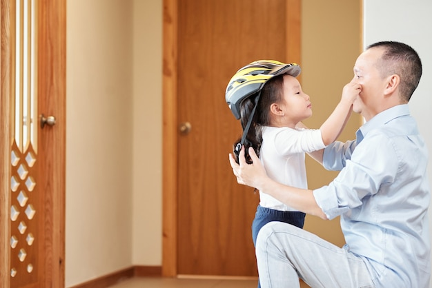 아파트를 떠나기 전에 그녀의 자전거 헬멧을 씌우고있는 그녀의 아버지의 얼굴을 만지고 귀여운 아시아 소녀