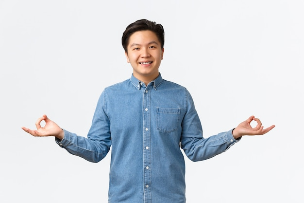 Cute asian man with braces meditating, smiling peaceful and relaxed, reaching nirvana or zen, standing in lotus pose with hands spread sideways, doing yoga exercises to chill, white background.