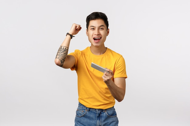 Cute asian man in yellow t-shirt celebrating while holds smartphone