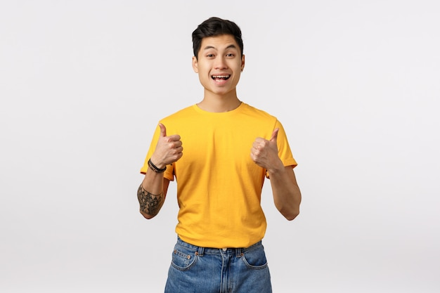 Cute asian man in yellow t-shirt giving thumbs up