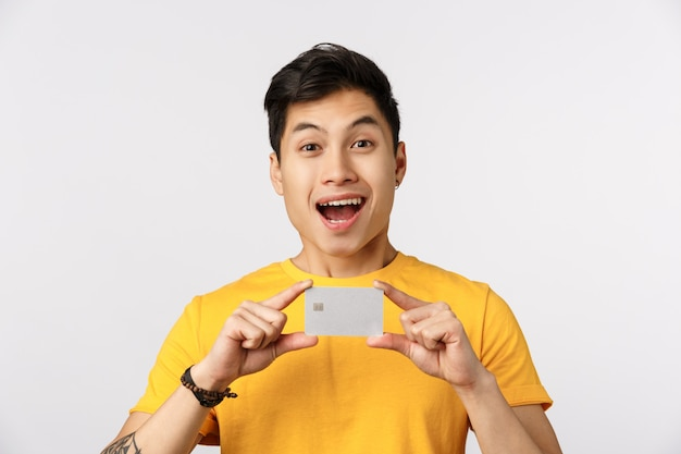 Cute asian man in yellow t-shirt holding blank business card