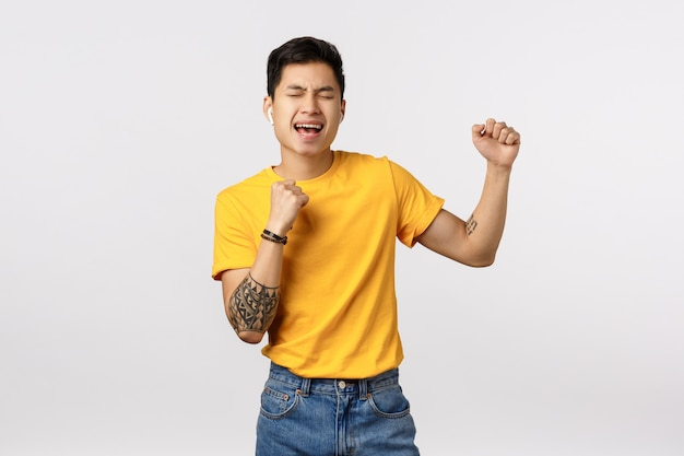 Cute asian man in yellow t-shirt listening to music in wireless earphones