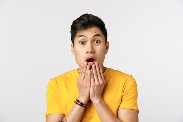 Cute asian man in yellow t-shirt with open mouth