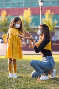 Cute asian mother and daughter wearing medical masks