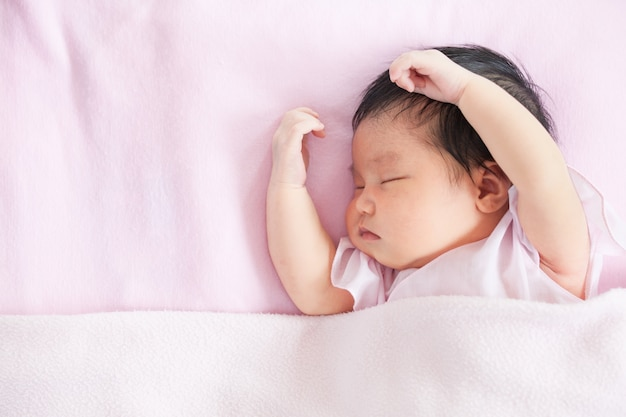 Cute asian newborn baby girl sleeping in bed with pink blanket ...