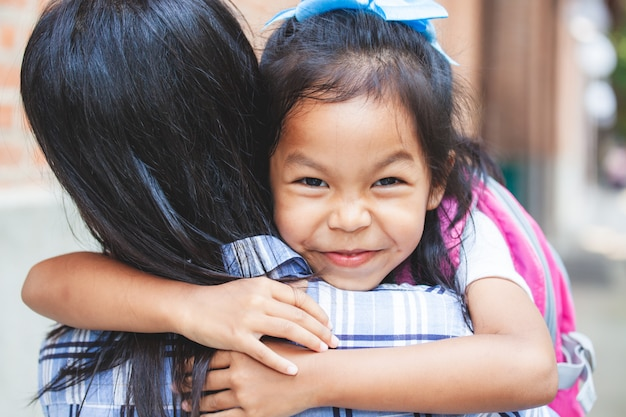 Cute asian pupil girl with backpack hugging her mother with happiness after back from school