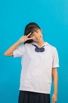 Cute asian schoolgirl showing two fingers on a blue .