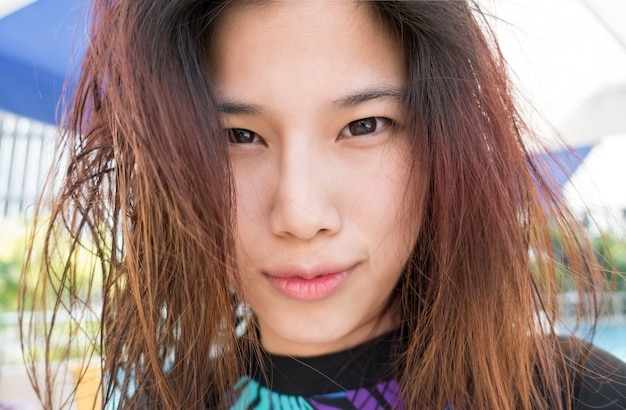 Cute asian surfer girl with messy hair on the beach