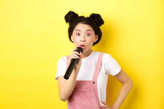 밝은 화장과 귀여운 아시아 십 대 소녀, 마이크 노래방에서 노래, 노란색 배경에 서