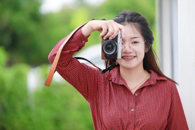 Симпатичная азиатская тайская девушка-подросток наслаждается цифровой камерой для фотографа-любителя.