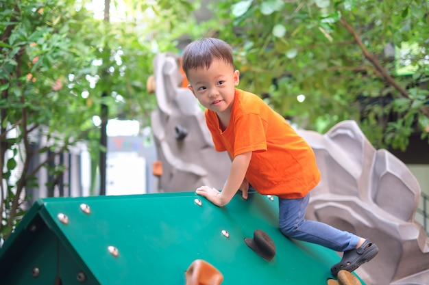 Cute asian toddler boy having fun trying to climb on artificial boulders at playground on nature