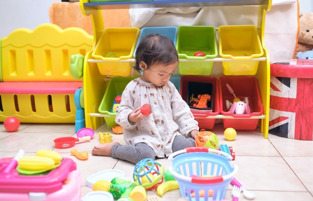 Cute asian toddler girl child sitting on floor having fun playing alone in playroom at home