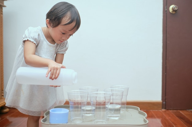 Cute asian toddler girl having fun playing with water table at home, wet pouring montessori preschool practical life activities, fine motor skills development
