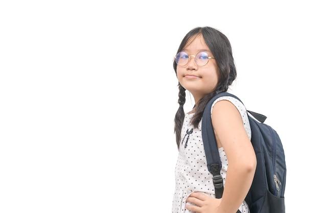 귀여운 아시아인은 흰색 배경에 학교 가방이 분리된 안경을 쓰고 학교 개념으로 돌아갑니다.