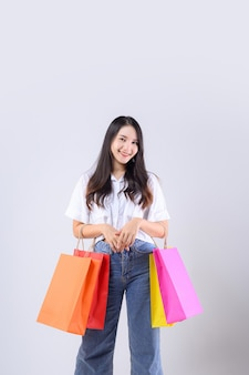 Cute asian woman carrying a multicolored shopping bag on white background.