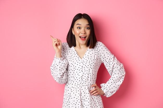 Carina donna asiatica in abito che punta in alto a sinistra copia spazio modello coreano che mostra pubblicità s...