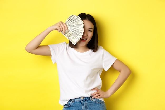 お金の後ろに顔を隠し、満足しているカメラをのぞき、現金を稼ぎ、黄色の背景の上に立っているかわいいアジアの女性。