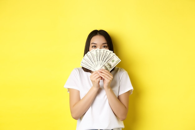 Cute asian woman hiding face behind money, peeking at camera satisfied, earn cash, standing over yellow.