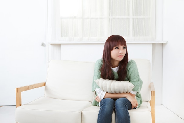 Cute asian woman in home on sofa.
