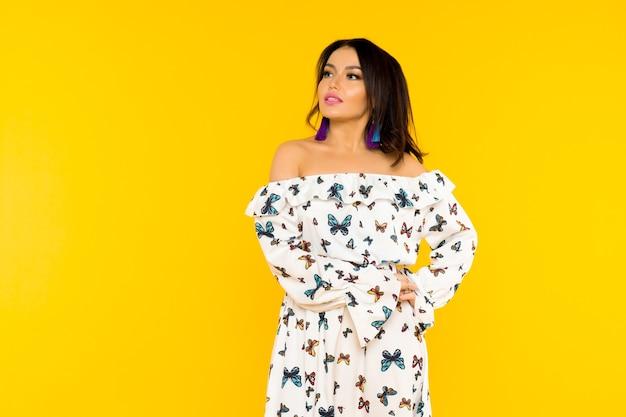 黄色の空間でポーズをとって蝶とシルクのドレスでかわいいアジアの女性