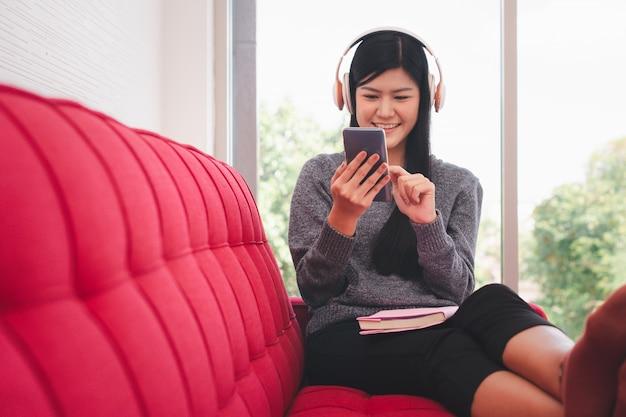 Симпатичная азиатская женщина сидит на диване утром и отправляет сообщения на мобильные телефоны