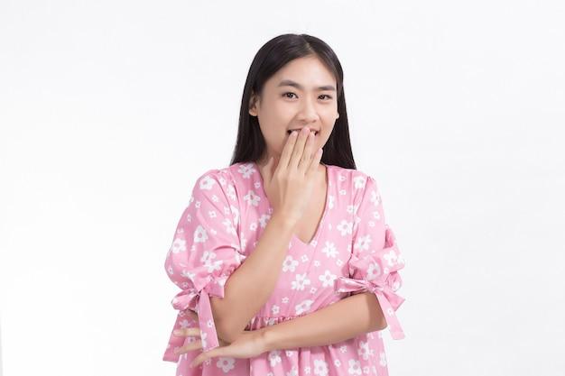 かわいいアジアの女性ピンクのドレス立っている笑顔口を閉じてまっすぐ見てください