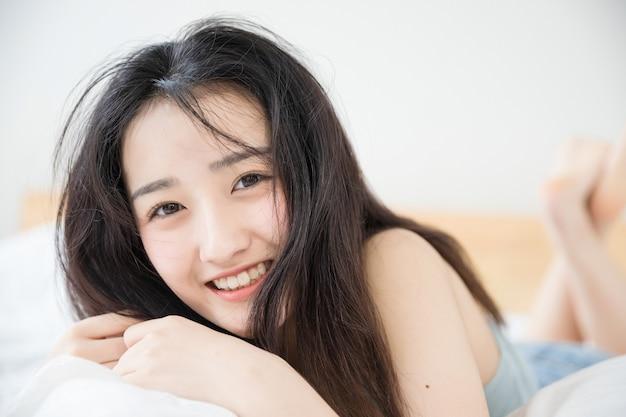 침대에서 쉬고 귀여운 아시아 여자